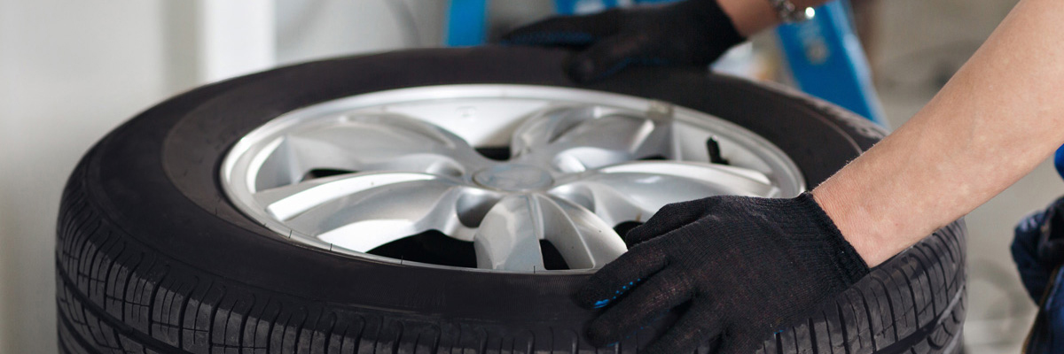 Mechanic selecting a tyre from stock - Tyres Sutton in Ashfield